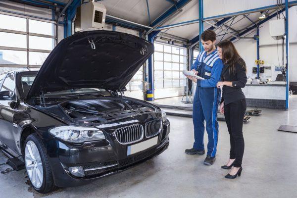 mechanic showing car to customer