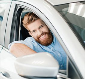 person smiling in car